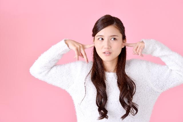 うるさい音で耳を抑える女性の画像